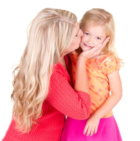 Mother kissing young daughter, isolated on white photo