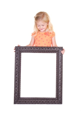 Child holding blank frame looking down, isolated on white photo
