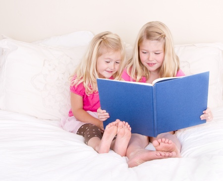 sibling: Sisters on bed reading book Stock Photo