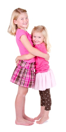 kids hugging: Sisters hugging full length on a white background Stock Photo