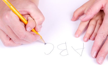 Mother helping daughter write alphabet, close up of hands and paper Stock fotó