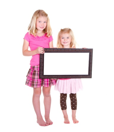 Two girls holding a blank frame room for copy space photo