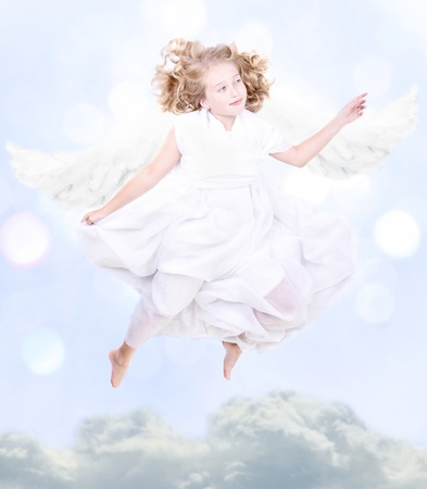angel flying: Young sweet angel flying above the clouds