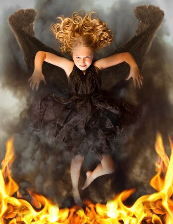 Young dark angel rising from the flames, with an evil look in her face and flames in her eyes. photo