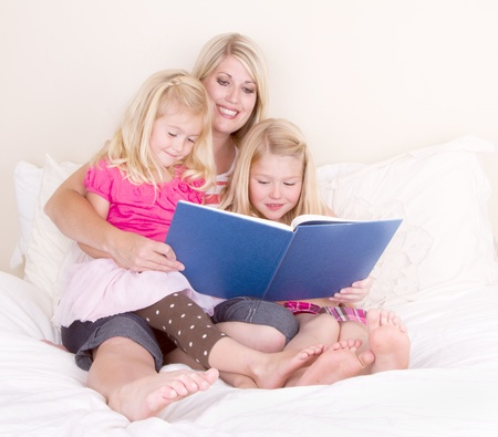 Family on bed reading book, mother and two daughters. Foto de archivo