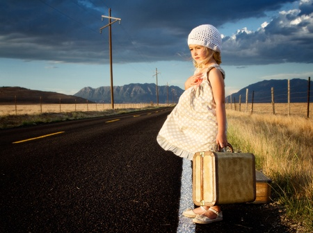 vintage clothing: Young girl on side of road with vintage suitcases in a mountain landscape