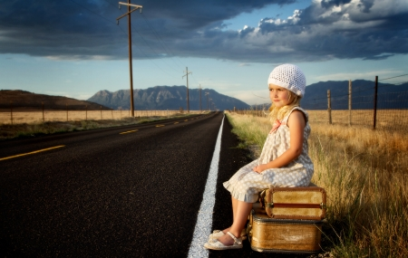 wait: Young girl on side of road with vintage suitcases in a mountain landscape