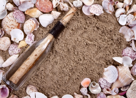 Message in a bottle on a sandy beach surrounded by seashells Stock Photo - 14667453