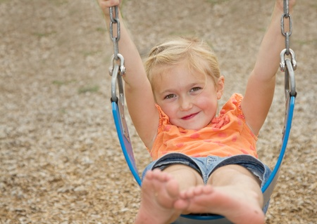 little girl or preschooler swinging on swing photo