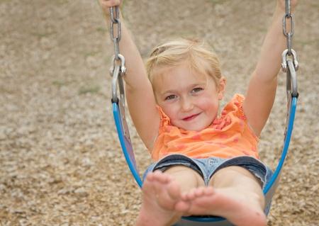little girl or preschooler swinging on swing Stock Photo