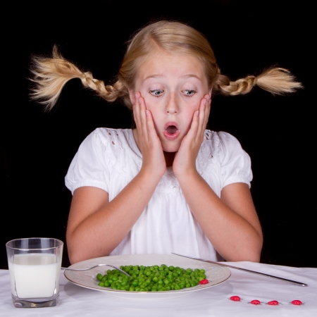 girl eating peas with bugs on the table isolated on black photo