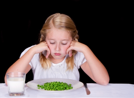 Child or teenager dislikes peas or vegtables, isolated on black