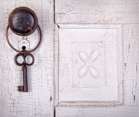 Vintage key hanging on a old cracked antique or vintage door photo