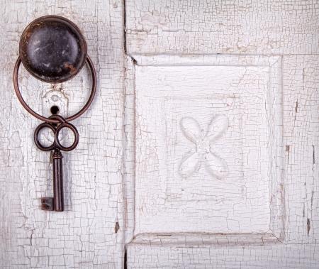 Vintage key hanging on a old cracked antique or vintage door