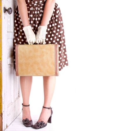antique suitcase: Retro image of a woman holding vintage luggage with a vintage door Stock Photo