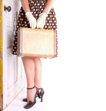 Retro image of a woman holding vintage luggage with a vintage door Banco de Imagens