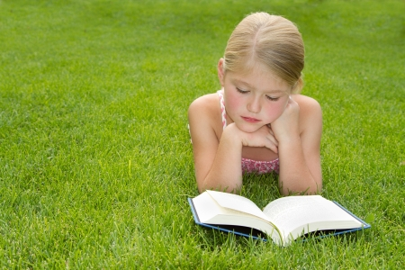 Girl reading outdoors in the grass Stock Photo
