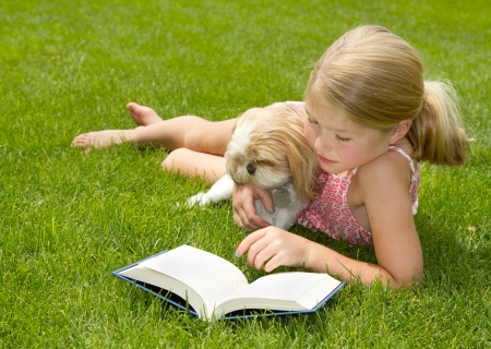 Girl reading with pet dog outdoors in the grass Foto de archivo