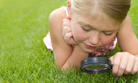 girl looking through magnifiying glass at grass outdoors photo