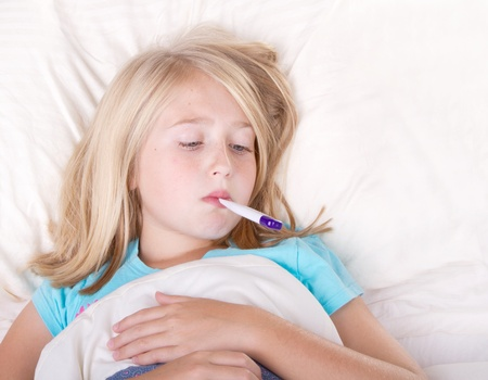 sick in bed: sick girl with a thermometer in mouth lying in bed Stock Photo