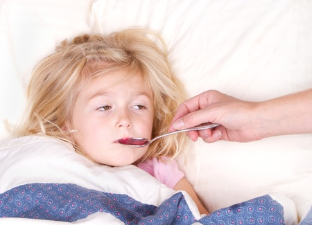 1 person: Sick child taking medicine from a spoon laying in bed