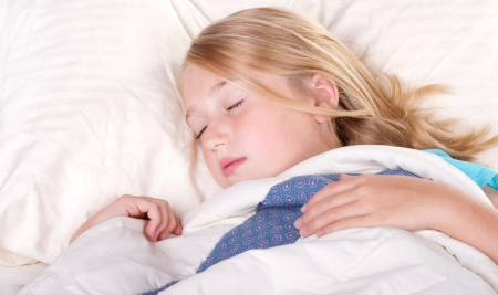 child or teen sleeping in bed photo