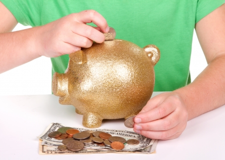 child putting money in a golden piggy bank photo
