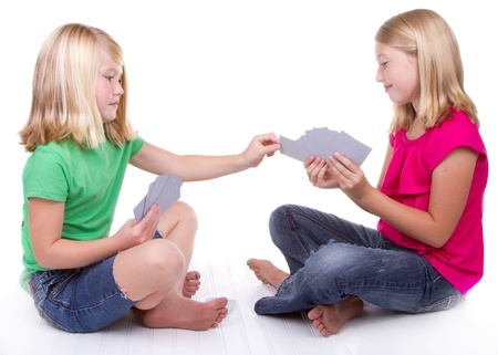 sisters or friends playing cards, white background Foto de archivo