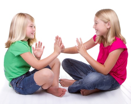 people clapping: two girls playing clapping game, white background Stock Photo