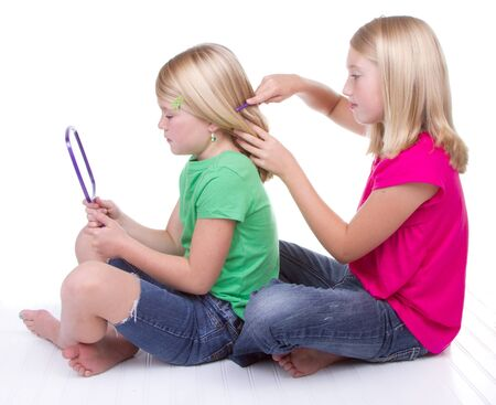 hair brush: sister combing younger sisters hair, white background
