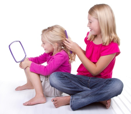 Older sister doing or combing younger sisters hair, white background Foto de archivo