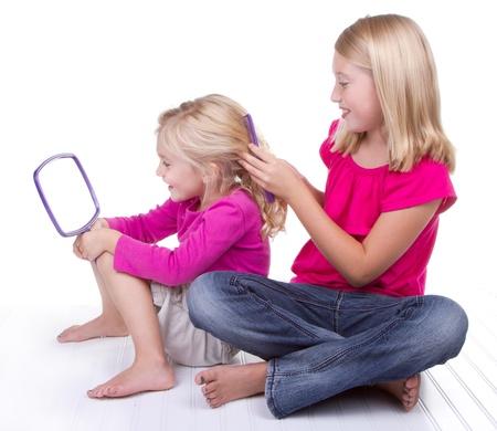 Oudere zus doen of kammen jongere zusjes haar, witte achtergrond Stockfoto