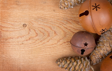 Chirstmas ornaments pinecones and rusty bells on a brown wood panel photo