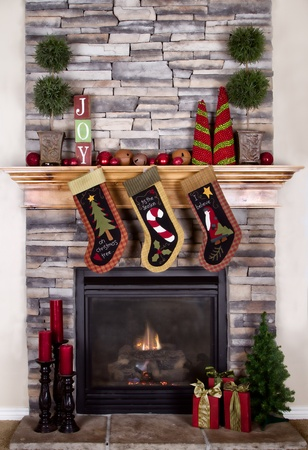christmas fireplace: Christmas stocking hanging from a mantel or fireplace, decorated for Christmas with fire glowing.