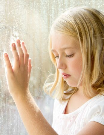 Child or teen looking down with hand on a rainy window photo