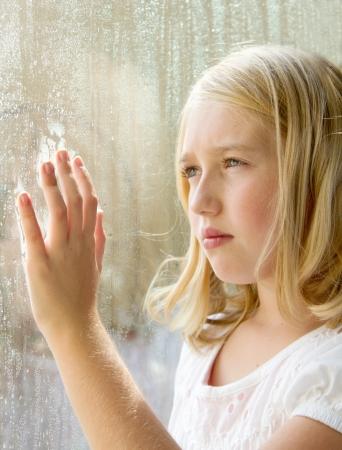 occhi tristi: Adolescente o bambino guardando fuori una finestra con pioggia