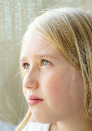 close-up of a teen or child looking out a rainy window photo