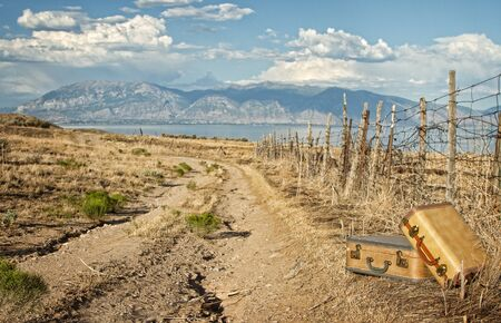 Vintage luggage sitting by a dirt road with mountains and lake photo