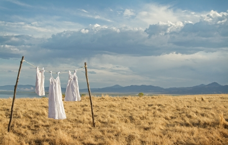 White dresses haning on a line in a rural mountain landscape Foto de archivo