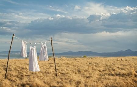 Witte jurken haning op een lijn in een landelijke berglandschap