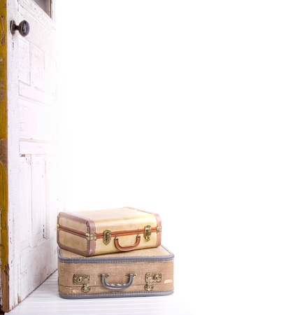 two vintage suitcases stacked by a vintage or antique door