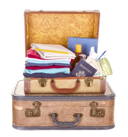 two vintage suitcases packed and open showing contents isolated on white Foto de archivo