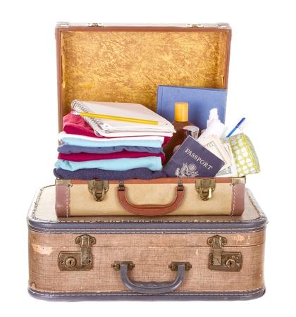maleta: dos maletas llenas de �poca y abiertos que muestran contenidos aislados en blanco Foto de archivo