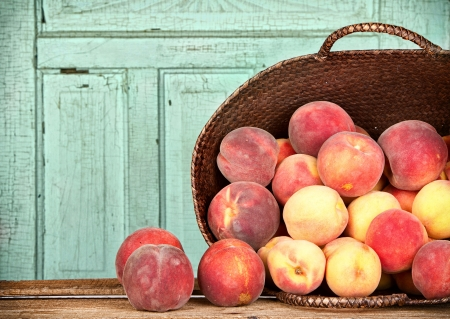 Many peaches spilling out of a basket Stock Photo