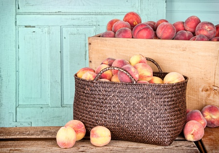 Many peaches in wooden crate and basket with antique panel background photo
