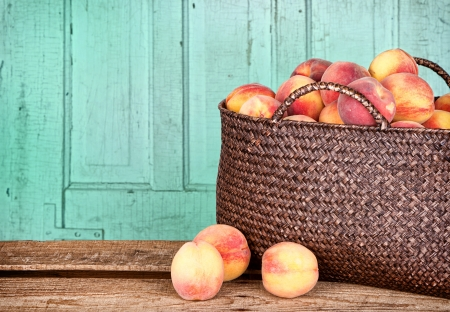 Many peaches in a basket with antique panel background photo