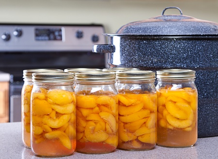 Canned peaches with large pot or canner in a kitchen
