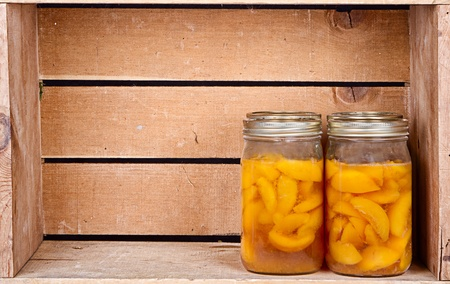 Canned homemade peaches in a rustic crate Stock Photo - 15252207