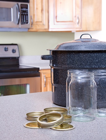 Canning jars with lids, canner or pot in a kitchen setting photo