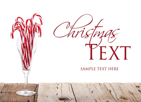 Many Candy canes in a wine glass on a wooden plank with an isolated white background photo